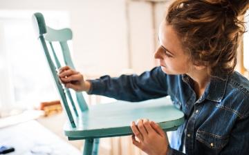 Eine junge Tischlerin in einem blau-türkis karrierten Hemd schleift einen hellgrünen Holzstuhl ab