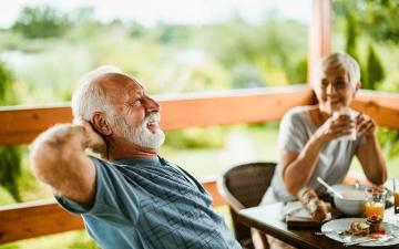 Älteres Paar sitzt auf der Terasse beim Frühstück. Es ist ein sonniger Morgen und das paar wirkt entspannt und zufrieden.