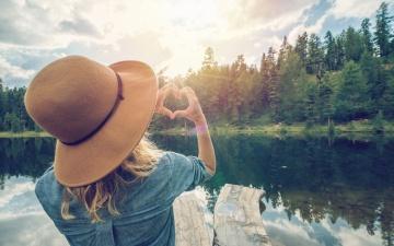 Eine Frau schaut über einen See auf das andere, bewaldete Ufer und formt mit Ihren Händen ein Herz. Es ist sonnig und die Landschaft spiegelt sich im klaren Wasser