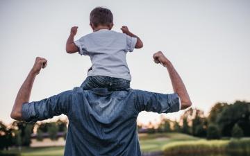Ein Vater hat seinen kleinen Sohn auf der Schulter. Beide spannen die Oberarme an um stärke zu zeigen. Man sieht die Rückenansicht