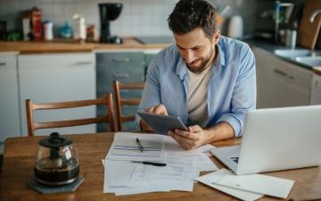 Mann sitzt mit Unterlagen, Laptop und Kaffee entspannt in der Küche und prüft seine Unterlagen. Er sieht erfreut und zufrieden aus.