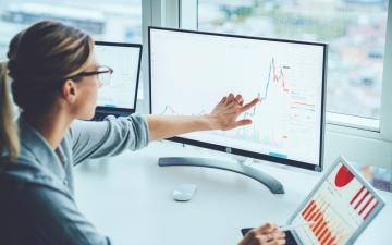 Eine Frau sitzt an Ihrem PC und prüft die Kursentwicklung ihres Portfolios. Dazu verwendet sie zusätzlich einen Laptop