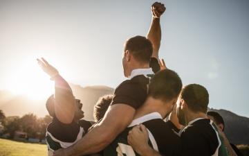 Eine kleine Sportlergruppe feiert den Sieg in einer Gruppenumarmung dabei werden 2 Arme in die Luft gestreckt